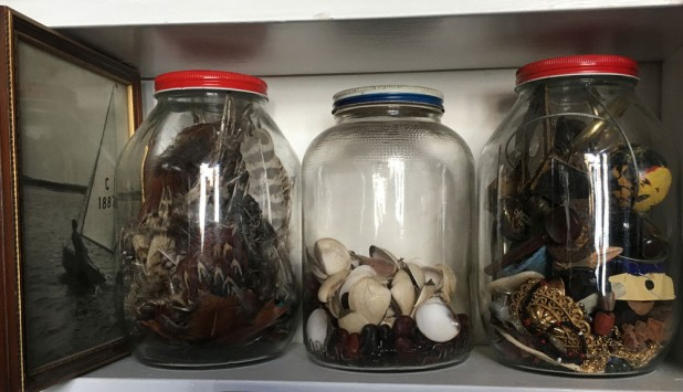 Jars full of pheasant feathers, shells and miscellaneous ephemera.