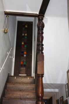 The staircase in our house. I made the door out of old floorboards and two knurl posts one on top of the other hold up the ceiling